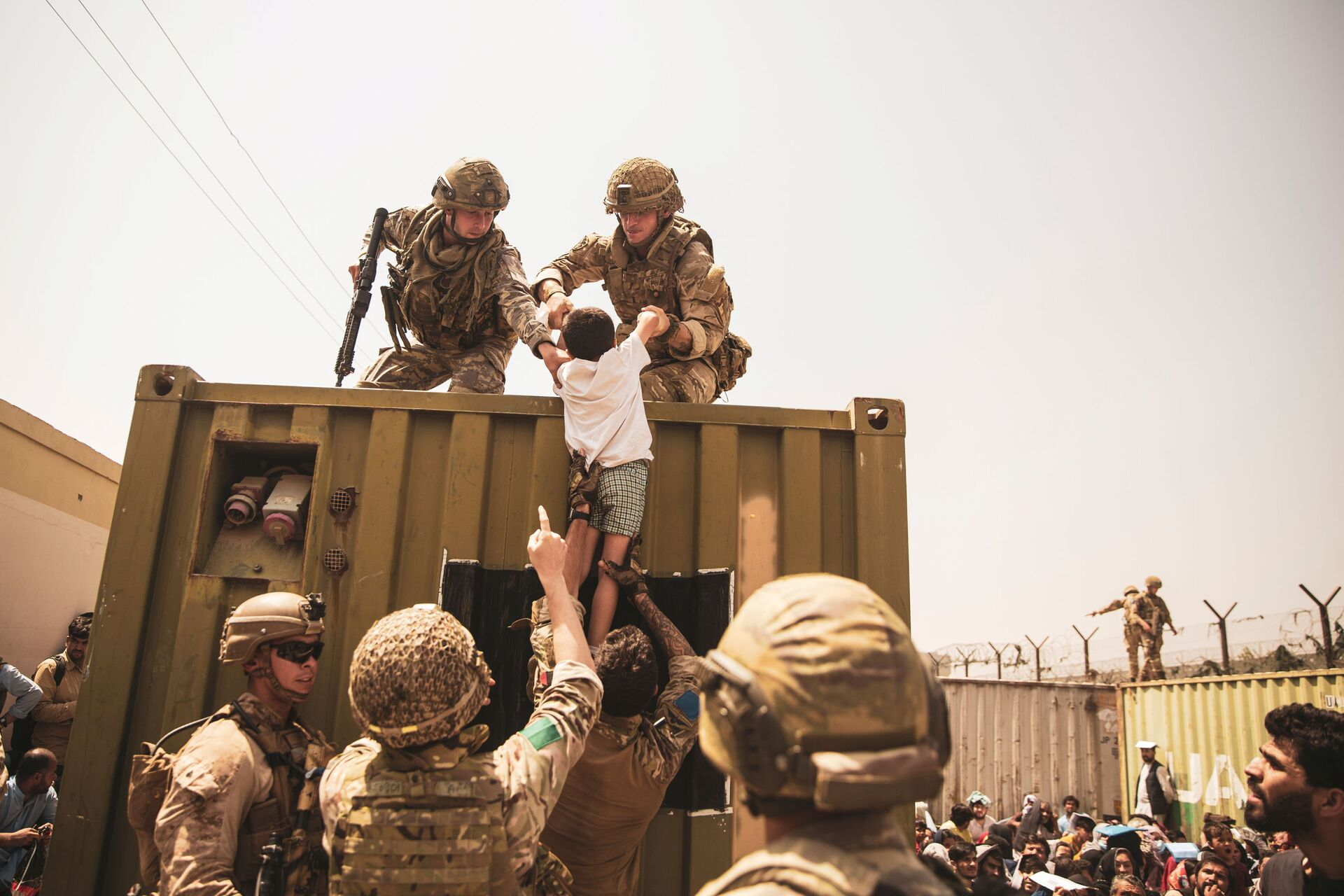 UK coalition forces, Turkish coalition forces, and U.S. Marines assist a child during an evacuation at Hamid Karzai International Airport, Kabul, Afghanistan, in this photo taken on August 20, 2021 - Sputnik International, 1920, 07.09.2021
