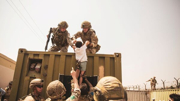 UK coalition forces, Turkish coalition forces, and U.S. Marines assist a child during an evacuation at Hamid Karzai International Airport, Kabul, Afghanistan, in this photo taken on August 20, 2021 - Sputnik International