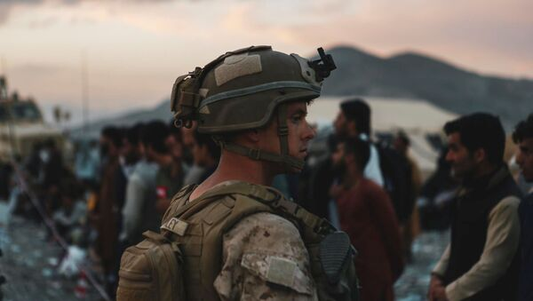 A Marine assigned to Special Purpose Marine Air Ground Task Force-Crisis Response-Central Command assists evacuees during an evacuation at Hamid Karzai International Airport, in Kabul, Afghanistan - Sputnik International