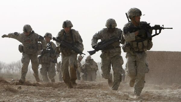 FILE - In this Feb. 14, 2010 file photo, a U.S. soldier returns fire as others run for cover during a firefight with insurgents in the Badula Qulp area, west of Lashkar Gah  in Helmand province, southern Afghanistan - Sputnik International