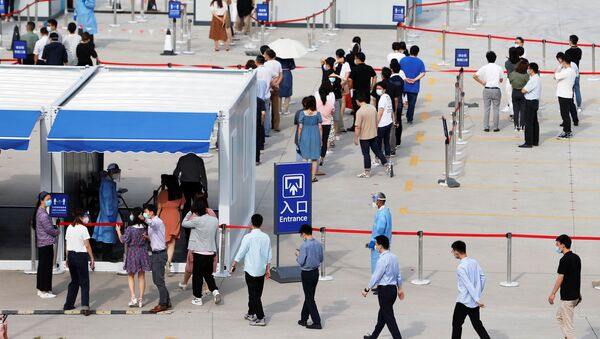 Staff members of Shanghai Pudong International Airport line up at a nucleic acid testing site to test for the coronavirus disease (COVID-19) in Shanghai, China August 20, 2021. Picture taken August 20, 2021. - Sputnik International