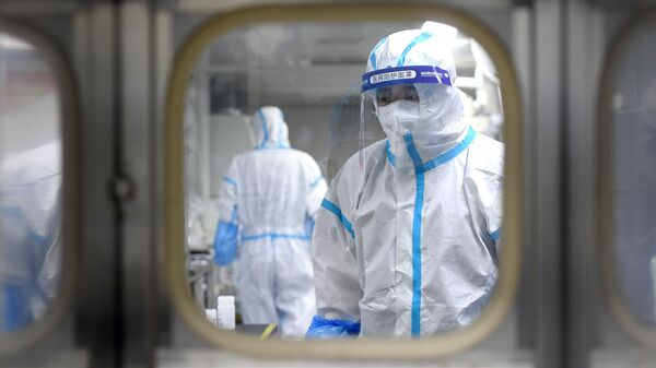 Medical workers in protective suits test nucleic acid samples inside a Huo-Yan (Fire Eye) laboratory of BGI, following new cases of the coronavirus disease (COVID-19) in Wuhan, Hubei province, China early August 5, 2021 - Sputnik International