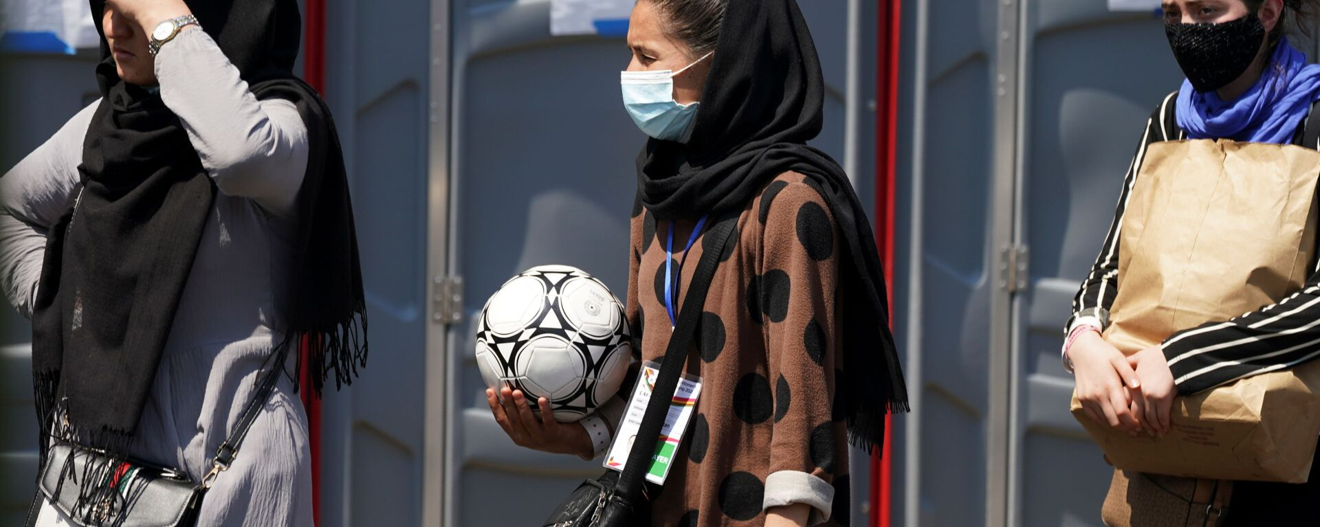 An Afghan woman holding a soccer ball and wearing a CAFA (Central Asian Football Association) credential, waits in line at a processing center for refugees evacuated from Afghanistan at the Dulles Expo Center near Dulles International Airport in Chantilly, Virginia, U.S., August 24, 2021 - Sputnik International, 1920, 20.09.2021