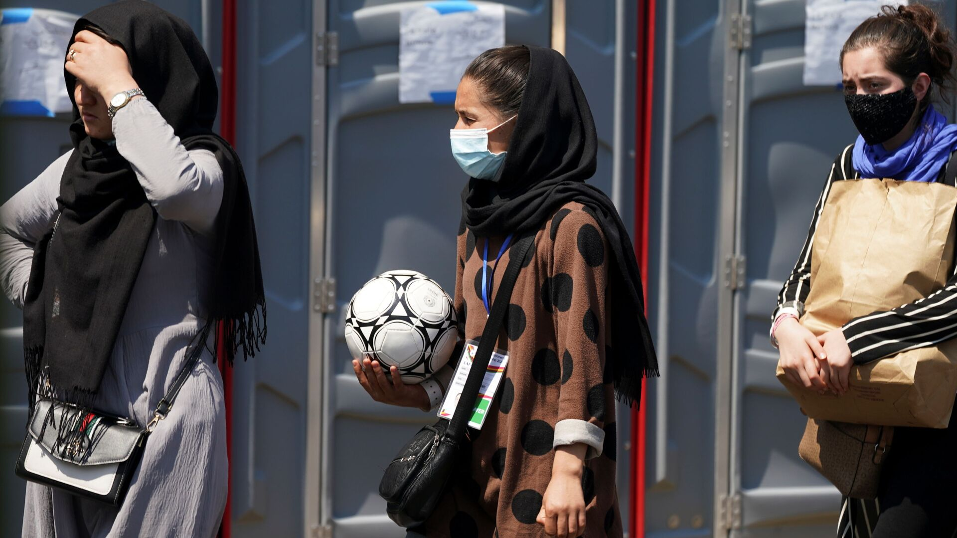 An Afghan woman holding a soccer ball and wearing a CAFA (Central Asian Football Association) credential, waits in line at a processing center for refugees evacuated from Afghanistan at the Dulles Expo Center near Dulles International Airport in Chantilly, Virginia, U.S., August 24, 2021 - Sputnik International, 1920, 15.09.2021