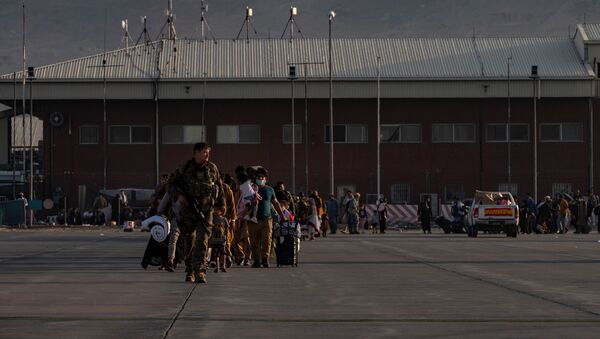 A U.S. Air Force Airman guides qualified evacuees aboard a U.S. Air Force C-17 Globemaster III at Hamid Karzai International Airport (HKIA), Afghanistan, August 24, 2021 - Sputnik International