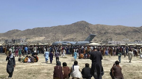 Hundreds of people gather near a US Air Force C-17 transport plane along the perimeter at the international airport in Kabul, Afghanistan, hoping to be evacuated. - Sputnik International