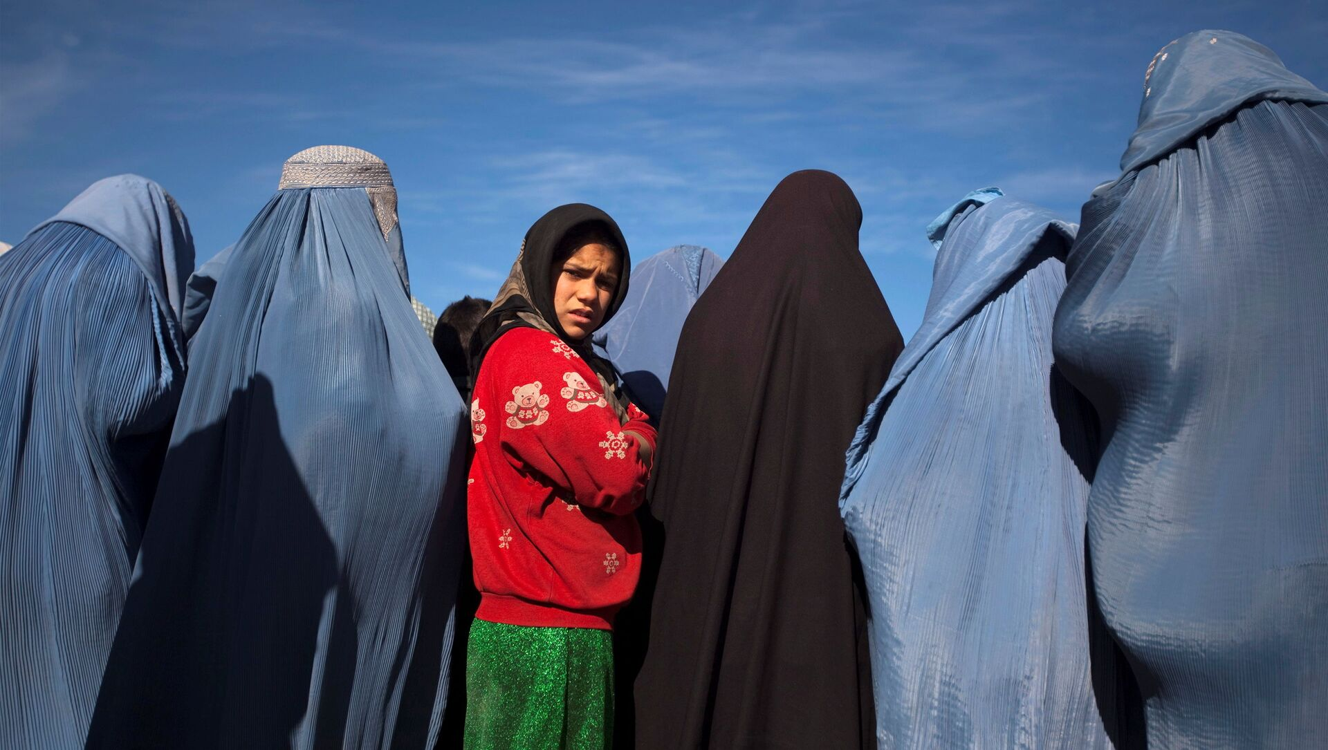 An Afghan girl stands among widows clad in burqas during a cash for work project by humanitarian organisation CARE International in Kabul, Afghanistan January 6, 2010 - Sputnik International, 1920, 27.08.2021