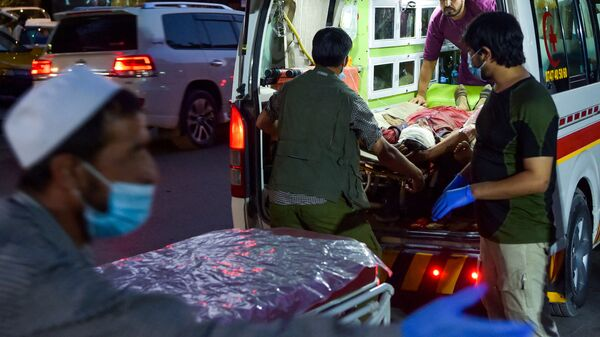 Medical staff bring an injured man to a hospital in an ambulance after two powerful explosions, which killed at least six people, outside the airport in Kabul on 26 August 2021. - Sputnik International