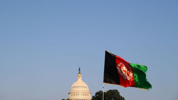 The dome of the U.S. Capitol is seen next to an Afghan flag as protesters take part in a demonstration challenging the transparency of the evacuation process from Kabul Airport, in Washington, U.S., August 28, 2021. - Sputnik International