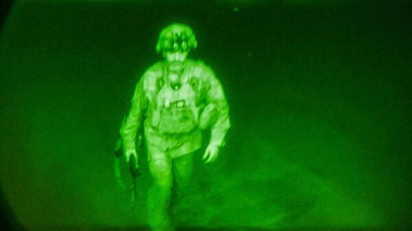 U.S. Army Major General Chris Donahue, commander of the 82nd Airborne Division, steps on board a C-17 transport plane as the last U.S. service member to leave Hamid Karzai International Airport in Kabul, Afghanistan August 30, 2021 in a photograph taken using night vision optics - Sputnik International