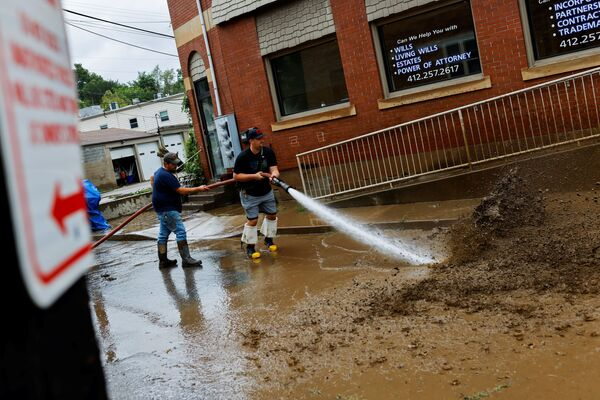 Members of the Oakdale Fire Department clear debris from the street after heavy rains from the storm Ida caused flooding in Oakdale, Pennsylvania, US, 1 September 2021.   - Sputnik International