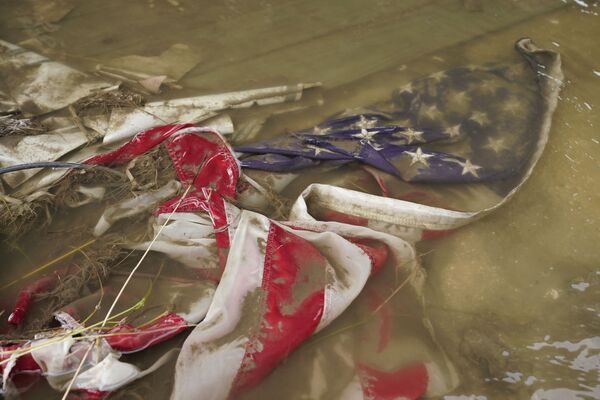 In the aftermath of Hurricane Ida, an American flag floats in a puddle of flood water Wednesday, 1 September 2021, in Myrtle Grove, Louisiana. - Sputnik International