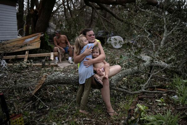 Tiffany Miller is embraced by her daughter Desilynn, 6, as she holds her one year old godchild Charleigh, after the family returned to their destroyed home in the aftermath of Hurricane Ida in Golden Meadow, Louisiana, US, 1 September 2021. - Sputnik International