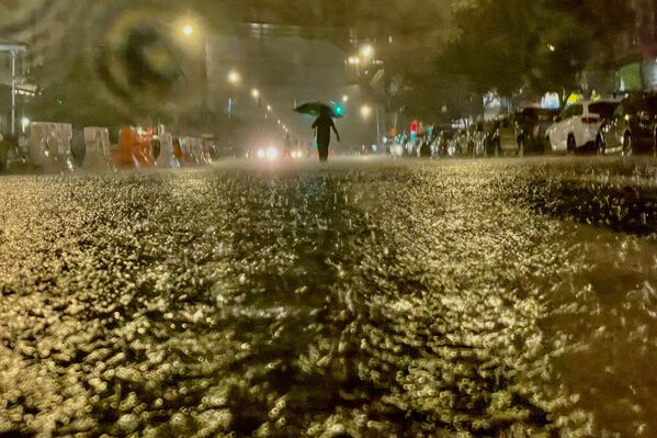 A person makes their way through rainfall amid the aftermath of Hurricane Ida on 1 September 2021, in the Bronx borough of New York City. The formerly Category 4 hurricane passed through New York City, dumping 3.15 inches of rain in the span of an hour at Central Park.    - Sputnik International