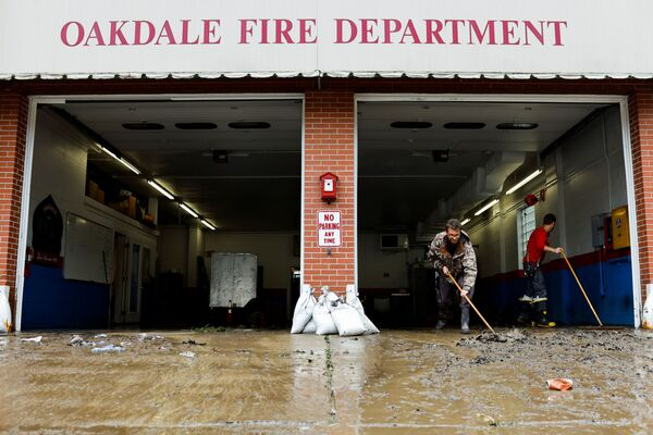 Members of the Oakdale Fire Department clear debris from their station after heavy rains from the storm Ida caused flooding in Oakdale, Pennsylvania, US, 1 September 2021.   - Sputnik International