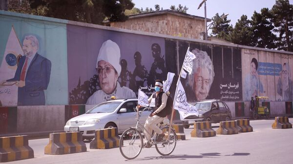 An Afghan man rides on his bicycle as he holds the Taliban flag in Kabul, Afghanistan, September 2, 2021.  - Sputnik International