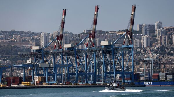 An Israeli military boat makes its way past cranes along the docks of the port of the northern city of Haifa, on June 24, 2021 - Sputnik International