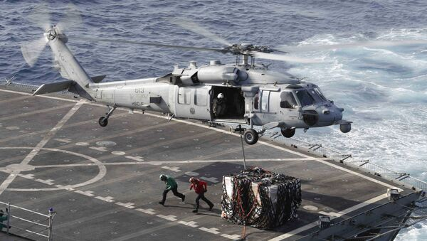 This handout picture released by the US Navy on May 19, 2019 shows a MH-60S Sea Hawk helicopter from the Nightdippers of Helicopter Sea Combat Squadron (HSC) 5 transporting cargo from the fast combat support ship USNS Arctic (T-AOE 8) to the Nimitz-class aircraft carrier USS Abraham Lincoln (CVN 72) during a replenishment-at-sea.  - Sputnik International
