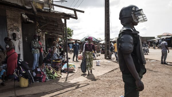 A Police officer stands guard at a round about after mass protests broke out, the morning after preliminary results were released for five communes in Conakry on October 21, 2020.  - Sputnik International