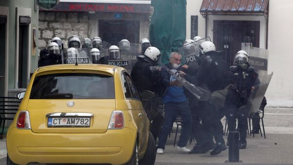 Police officers detain a man during a protest against the enthronement of Bishop Joanikije in Cetinje, Montenegro - Sputnik International