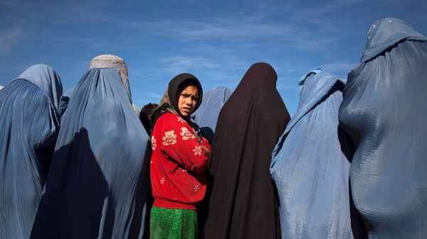 An Afghan girl stands among widows clad in burqas during a cash for work project by humanitarian organisation CARE International in Kabul - Sputnik International