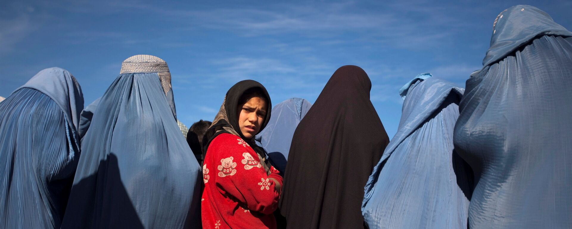 An Afghan girl stands among widows clad in burqas during a cash for work project by humanitarian organisation CARE International in Kabul - Sputnik International, 1920, 07.09.2021