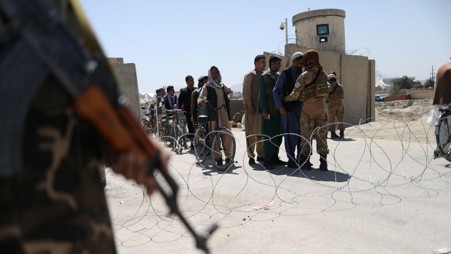 Taliban members pat down workers leaving the military airfield in Kabul, Afghanistan, September 5, 2021 - Sputnik International, 1920, 14.09.2021