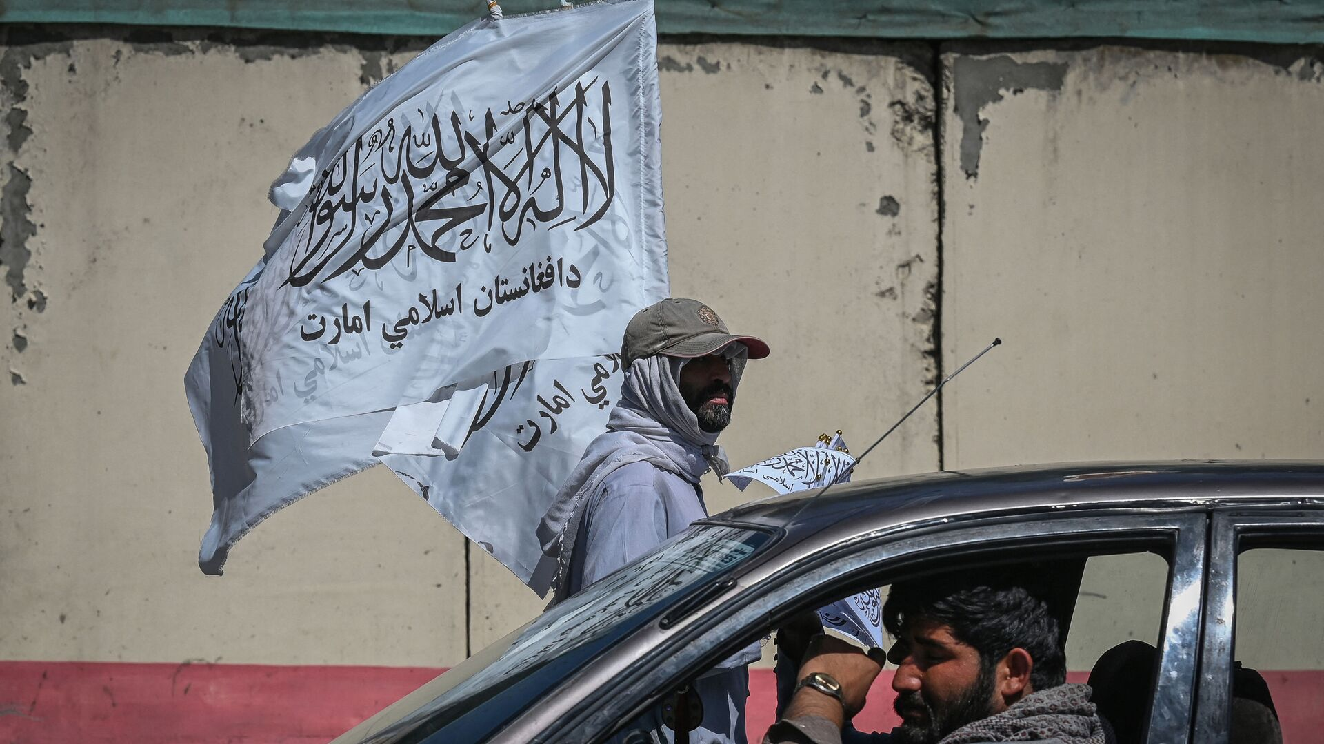 A mobile hawker carries Taliban flags as commuters make their way along a road in Kabul on September 5, 2021.  - Sputnik International, 1920, 06.09.2021