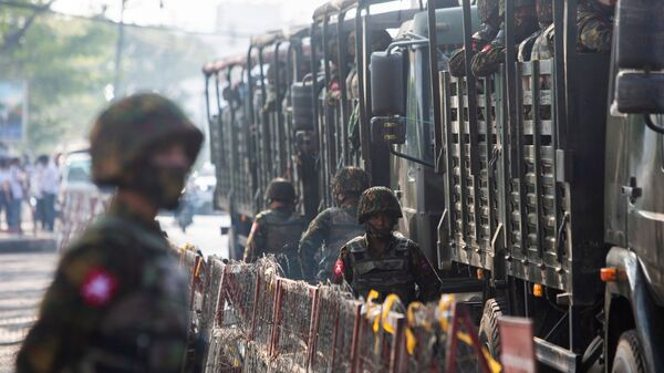 Soldiers stand next to military vehicles as people gather to protest against the military coup, in Yangon, Myanmar, February 15, 2021. - Sputnik International