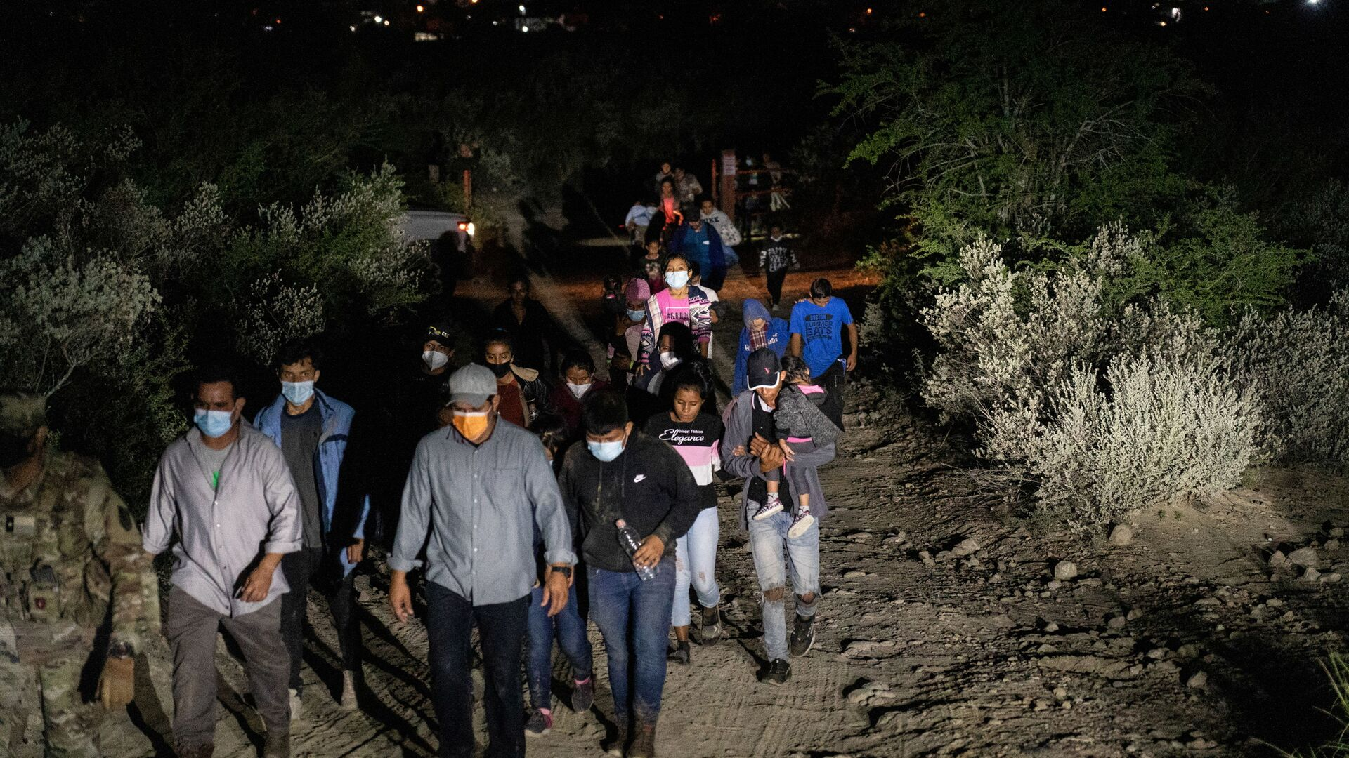Asylum-seeking migrant families are escorted out of a private property by the U.S. National Guard after crossing the Rio Grande river into the United States from Mexico in Roma, Texas, U.S., August 14, 2021 - Sputnik International, 1920, 07.09.2021