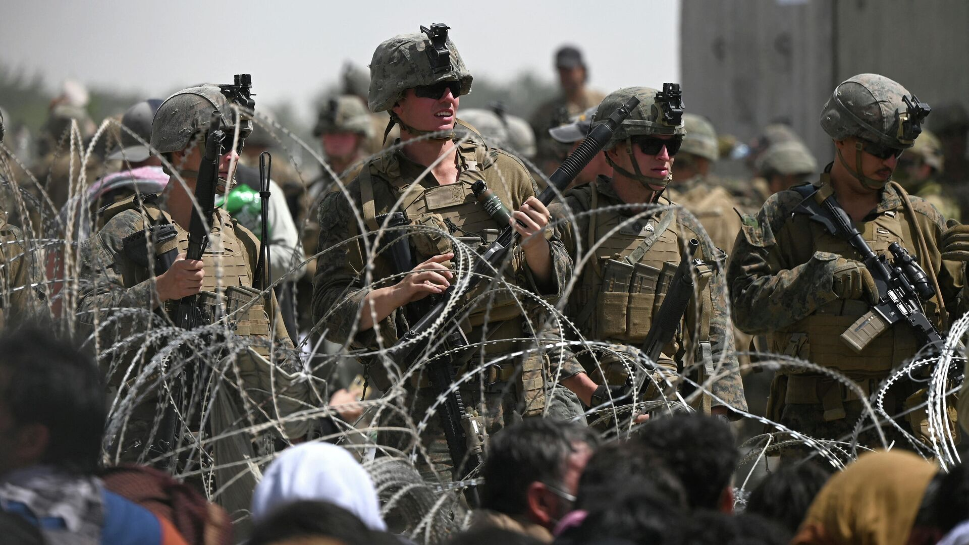 US soldiers stand guard behind barbed wire as Afghans sit on a roadside near the military part of the airport in Kabul on August 20, 2021, hoping to flee from the country after the Taliban's military takeover of Afghanistan - Sputnik International, 1920, 17.09.2021