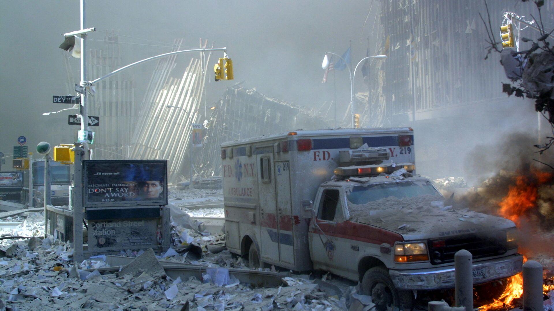 Поврежденный автомобиль скорой помощи и покрытая обломками улица после обрушения первого здания Всемирного торгового центра в Нью-Йорке - Sputnik International, 1920, 11.09.2021