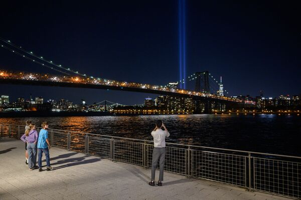 """People take photos from the Brooklyn waterfront of a light installation entitled """"Tribute in Light"""" commemorating the 9/11 terrorist attacks, in New York on 10 September 2021. - Sputnik International"""