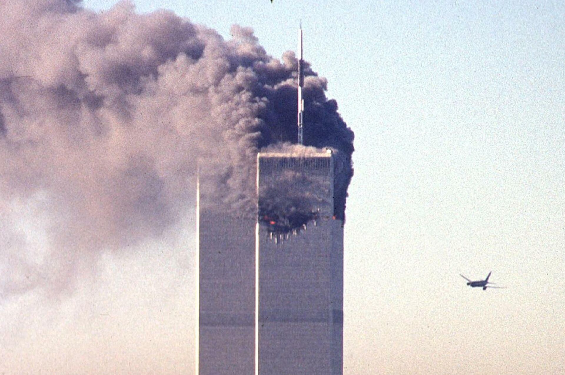 (FILES) In this file photo taken on September 11, 2001, a hijacked commercial aircraft approaches the twin towers of the World Trade Center shortly before crashing into the landmark skyscraper in New York.  - Sputnik International, 1920, 11.09.2021