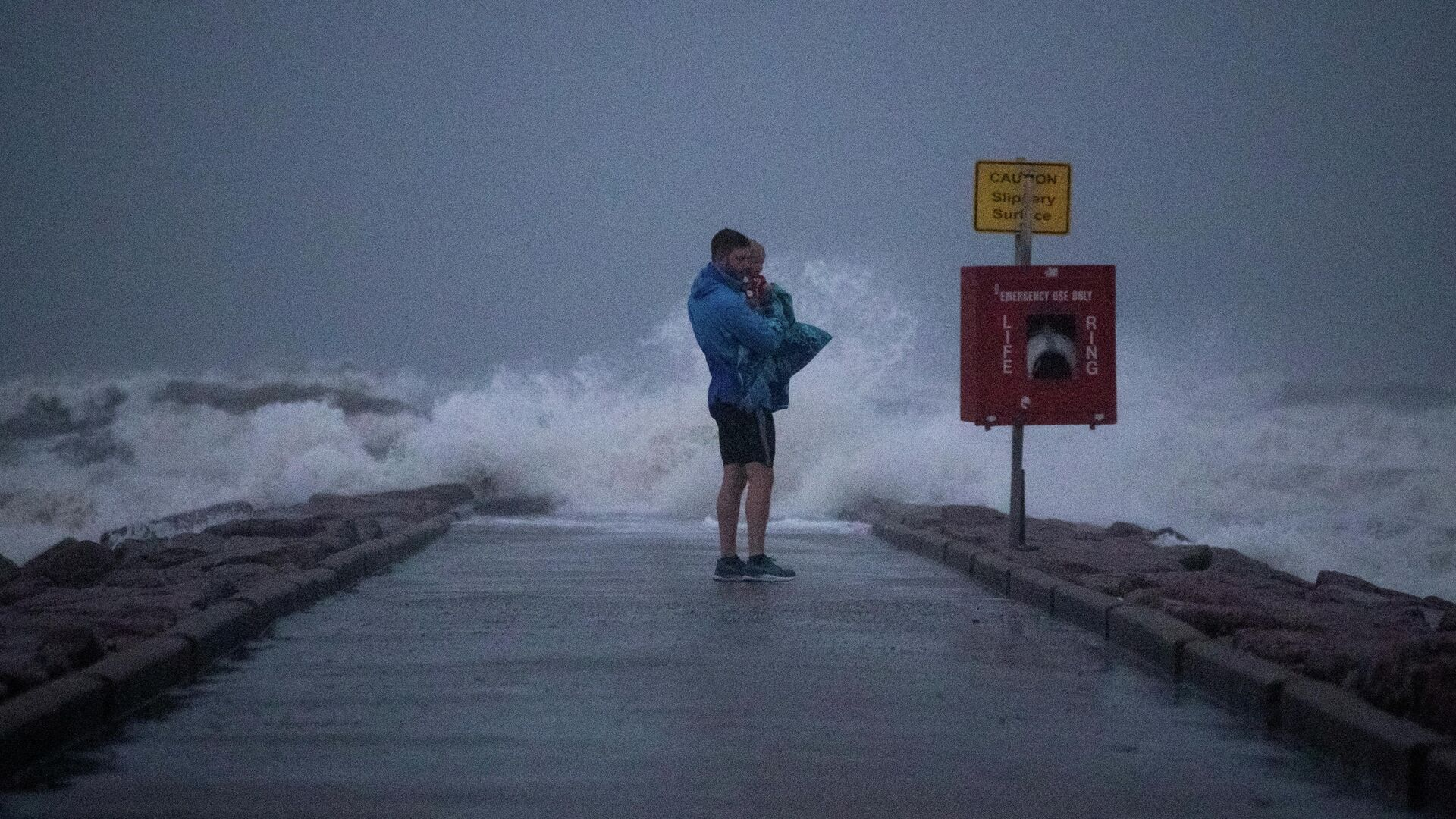 Local resident John Smith holds his 18-month-old son Owen as he stands near breaking waves on a pier ahead of the arrival of Tropical Storm Nicholas in Galveston, Texas, U.S., September 13, 2021. - Sputnik International, 1920, 14.09.2021