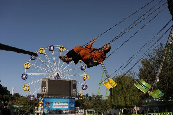 An Afghan woman enjoys a carousel ride at an amusement park in Kabul, Afghanistan, 13 September 2021.  - Sputnik International