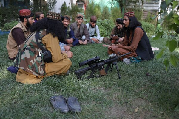 A rifle lies on the ground as Taliban soldiers sit in an amusement park in Kabul, Afghanistan, 13 September 2021.  - Sputnik International