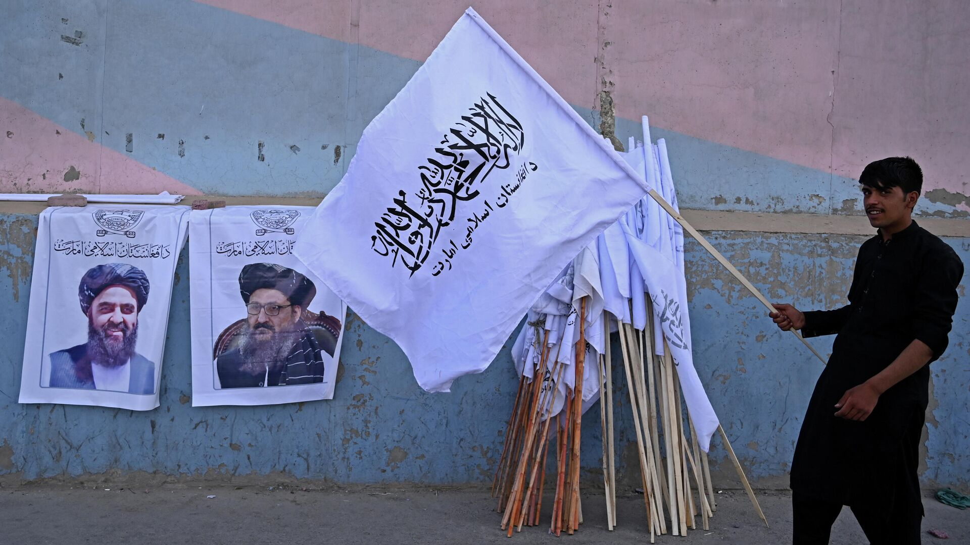 A vendor holds a Taliban flag next to the posters of Taliban leaders Mullah Abdul Ghani Baradar and Amir Khan Muttaqi (L) as he waits for customers along a street in Kabul on August 27, 2021, following the Taliban's military takeover of Afghanistan - Sputnik International, 1920, 22.09.2021