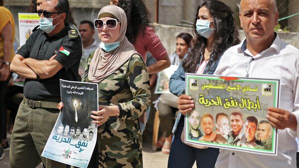 People gather with signs for a demonstration in support of Palestinian prisoners held in Israeli prisons, outside the offices of the International Committee of the Red Cross (ICRC) in Ramallah in the occupied West Bank on September 14, 2021 - Sputnik International