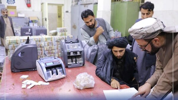 Men are pictured as Afghanistan's Taliban-controlled central bank seizes a large amount of money in cash and gold from former top government officials, including former vice president Amrullah Saleh, in Afghanistan, in this handout obtained by Reuters on September 15, 2021 - Sputnik International
