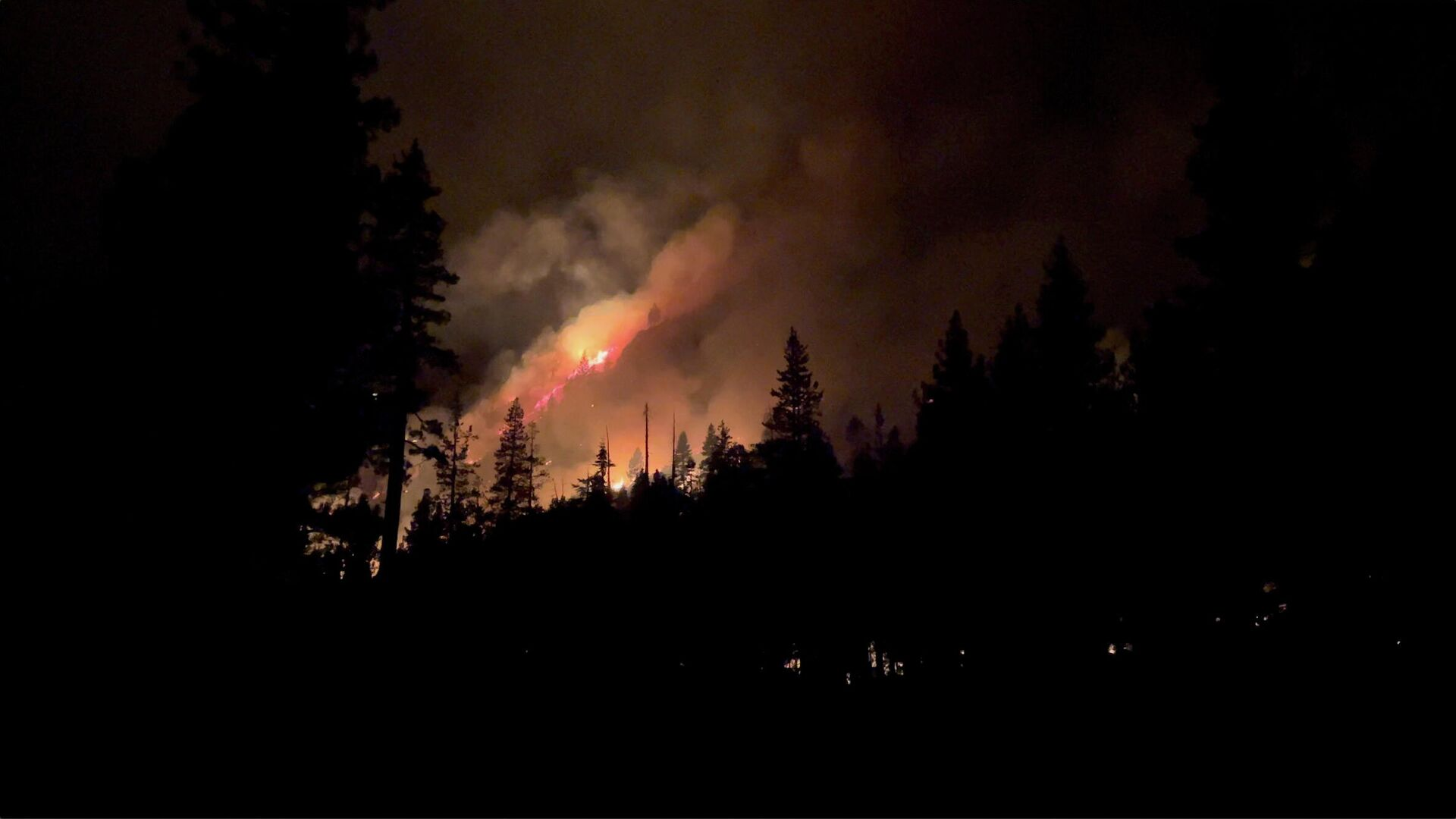 Smoke and flames are seen amid an early morning wildfire in South Lake Tahoe, California, U.S. August 31, 2021, in this still image from video obtained via social media - Sputnik International, 1920, 16.09.2021