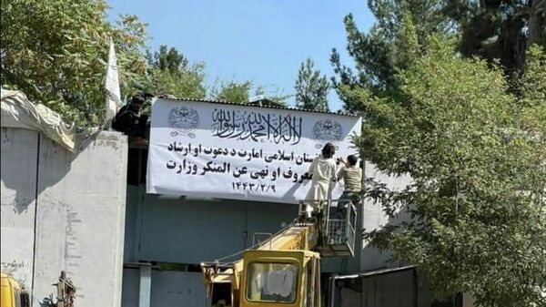 People on a mechanical crane attend to a white signboard outside a building which reads Islamic Emirate of Afghanistan and Ministries of prayer and guidance and the Promotion of Virtue and Prevention of Vice in Kabul, Afghanistan, September 17, 2021 in this picture obtained from social media - Sputnik International