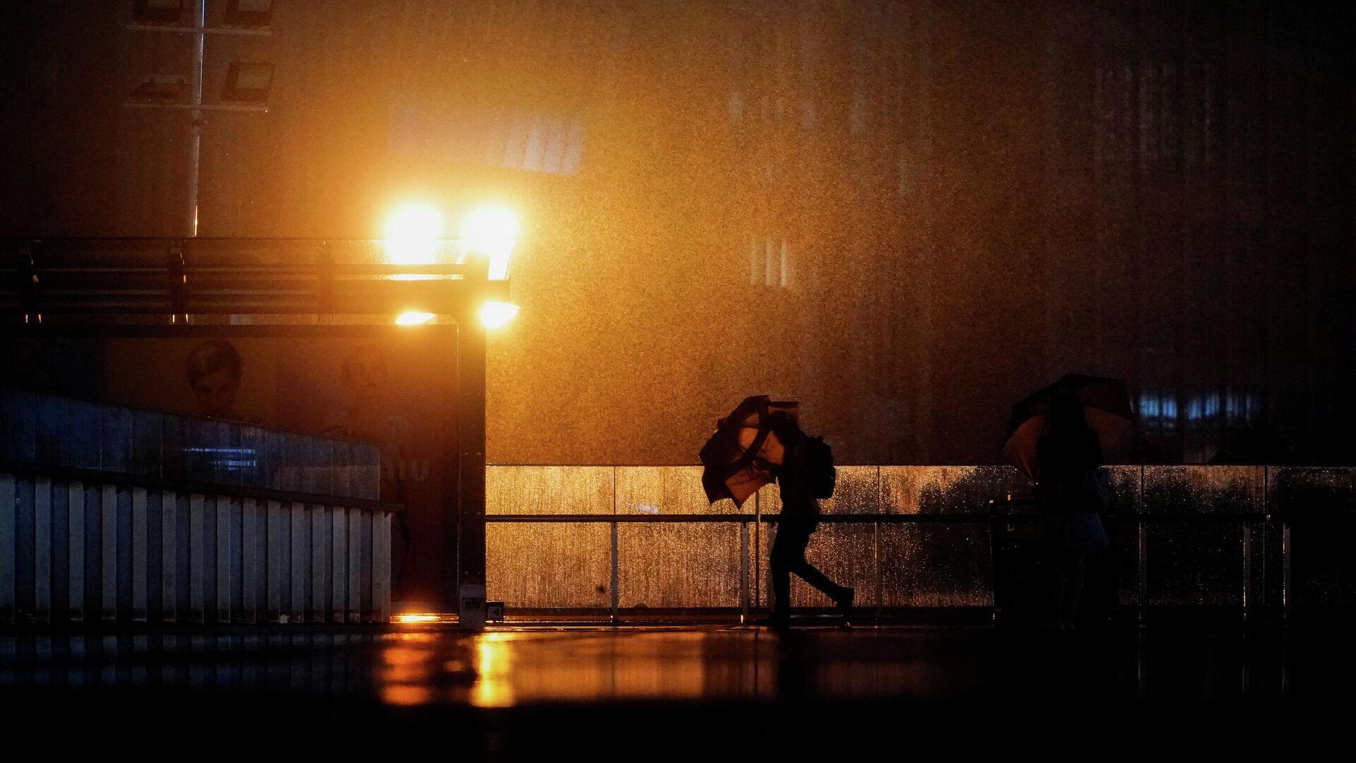 A man walks with an umbrella amid rainfall, as Typhoon Chanthu approaches, in Shanghai, China September 13, 2021. - Sputnik International, 1920, 18.09.2021