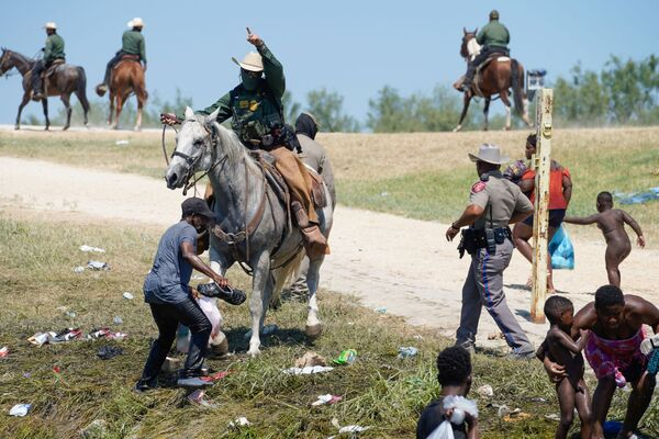 EDITORS NOTE: Graphic content / A United States Border Patrol agent on horseback tries to stop a Haitian migrant from entering an encampment on the banks of the Rio Grande near the Acuna Del Rio International Bridge in Del Rio, Texas on 19 September 2021.  - Sputnik International