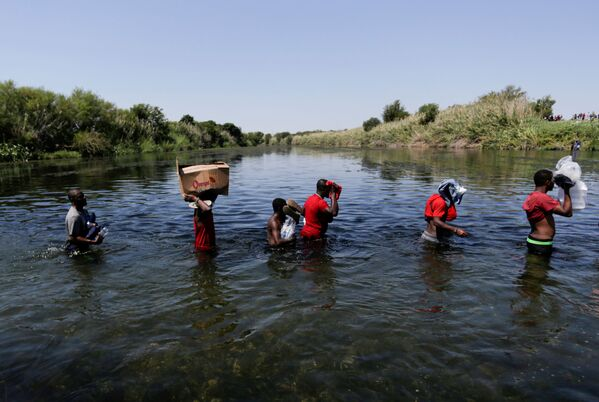 FILE PHOTO: Would-be immigrants wade through the Rio Grande river to cross the border between Ciudad Acuna, Mexico and Del Rio, Texas, US, after buying supplies on the Mexican side, in Ciudad Acuna, Mexico, 19 September  2021. - Sputnik International