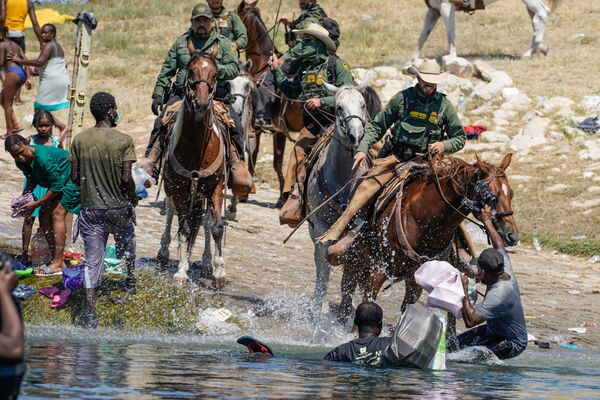 United States Border Patrol agents on horseback attempt to stop Haitian migrants from entering an encampment on the banks of the Rio Grande near the Acuna Del Rio International Bridge in Del Rio, Texas on 19 September 2021.  - Sputnik International