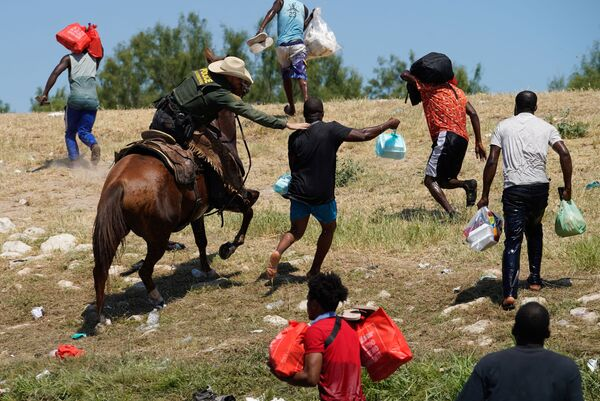 A United States Border Patrol agent on horseback tries to stop a Haitian migrant from entering an encampment on the banks of the Rio Grande near the Acuna Del Rio International Bridge in Del Rio, Texas on 19 September 2021. - Sputnik International