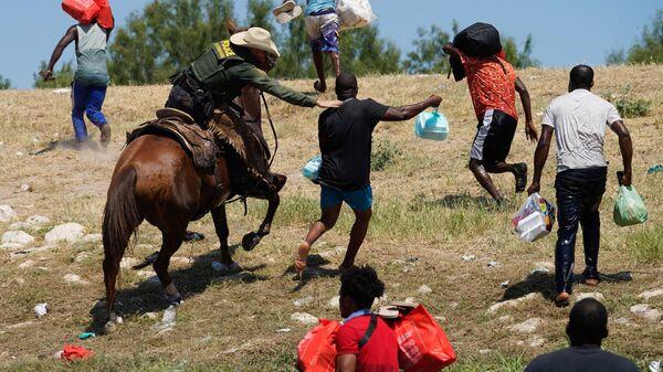 Агент пограничного патруля США пытается помешать гаитянскому мигранту войти в лагерь на берегу Рио-Гранде в Дель-Рио, штат Техас - Sputnik International