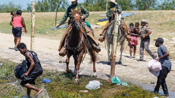 Агенты пограничного патруля США пытаются помешать гаитянским мигрантам войти в лагерь на берегу Рио-Гранде в Дель-Рио, штат Техас - Sputnik International
