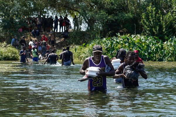 Haitian migrants, part of a group of over 10,000 people staying in an encampment on the US side of the border, cross the Rio Grande to get food and water in Mexico,  after another crossing point was closed near the Acuna Del Rio International Bridge in Ciudad Acuna, Mexico on 19 September 2021.  - Sputnik International